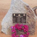 Commemorative ANZAC plaque mounted a large rock with wreath of flowers