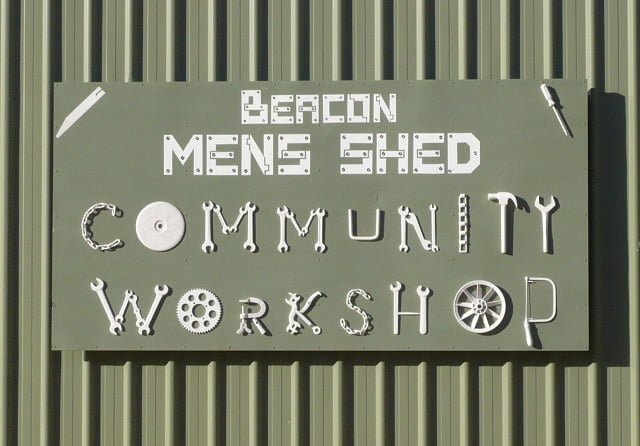the Beacon Mens Shed sign mounted on outside steel wall of workshop