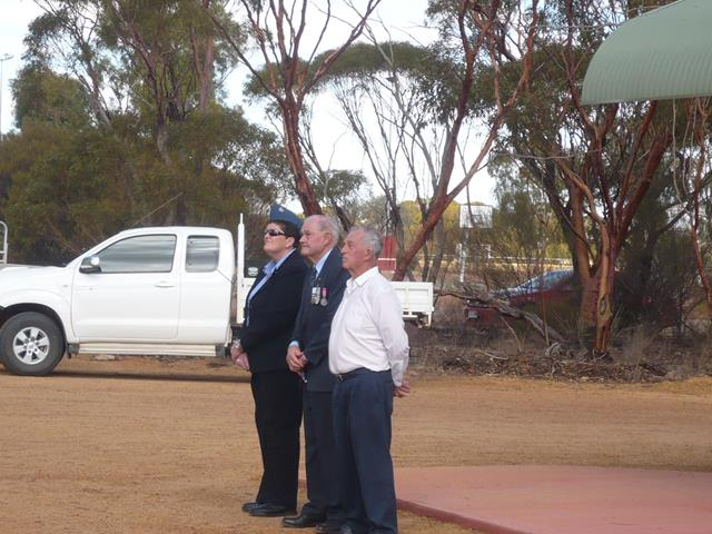 Beacon locals standing to the flag at the 2011 Anzac service in Beacon, Western Australia