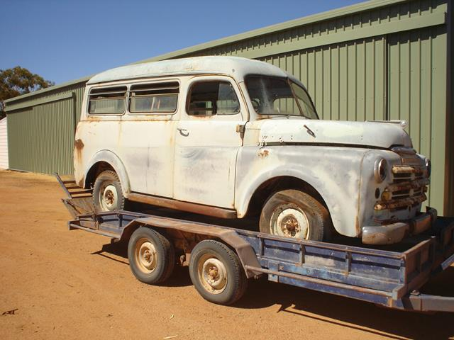 An old car arrives on a trailer to be restored by the Beacon Mens Shed