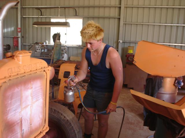 volunteer appling spray painting to Allis Chalmers tractor front