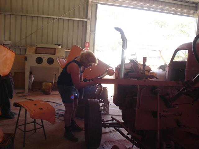volunteer inspects a small part of the Allis Chalmers tractor