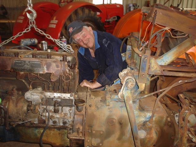 Volunteer lifting engine out of vintage Allis Chalmers tractor