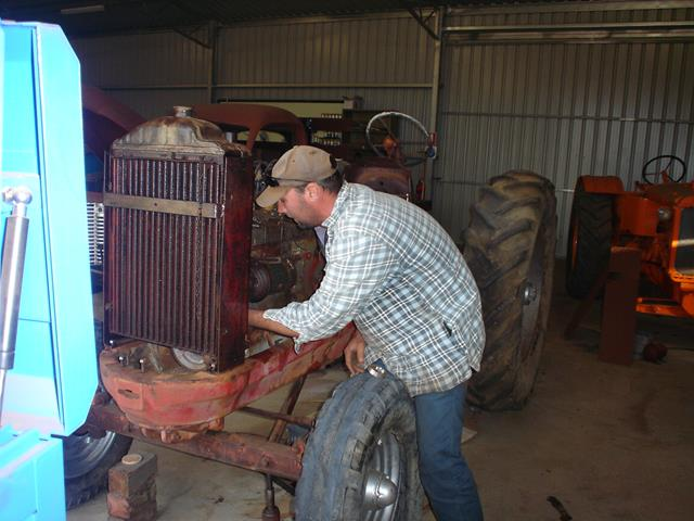 volunteer disassembling vintage Allis Chalmers tractor