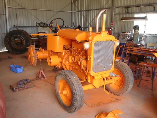 Very bright orange Allis Chalmers restored tractor seen from the front right side