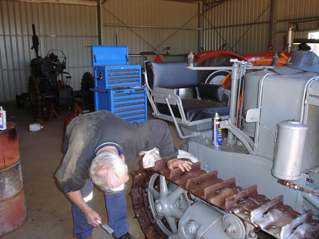 A volunteer applies grey paint as part of the restoration to the exterior the Holt Caterpillar