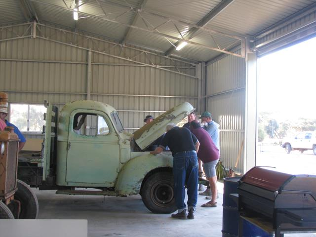 Everyone looking under the hood of the International truck restoration