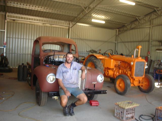 Volunteer Dale Andrews posing in front of unrestored International truck