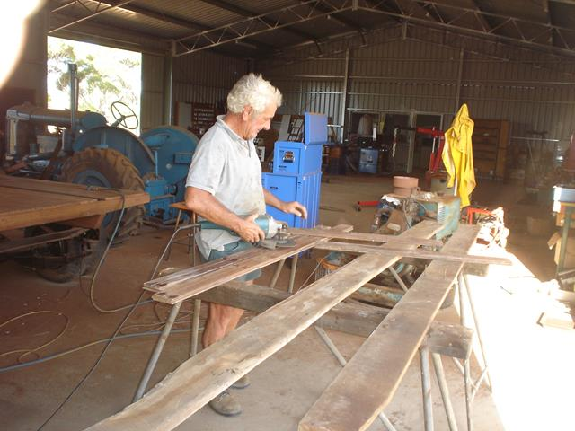 volunteer cutting wood planks for the tray on the International Truck restoration