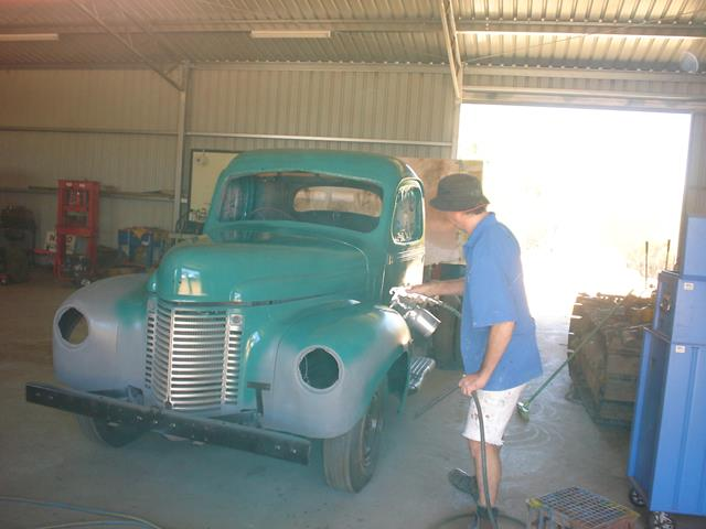 A volunteer spray painting the International truck as part of the restoration