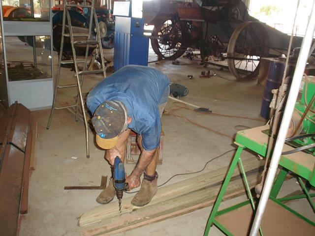 Beacon Mens Shed volunteer drilling some wood planks on shed floor