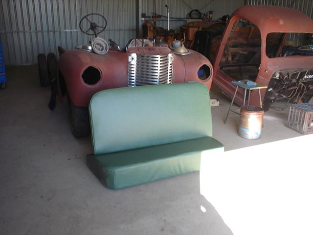 Newly recovered green vinyl bench seat waiting to be installed International truck restoration